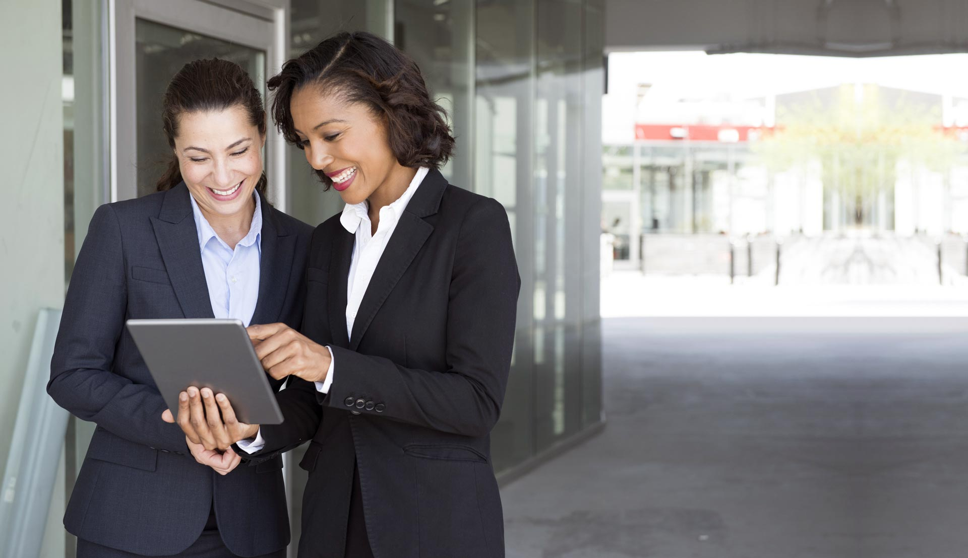 Two business women with a tablet