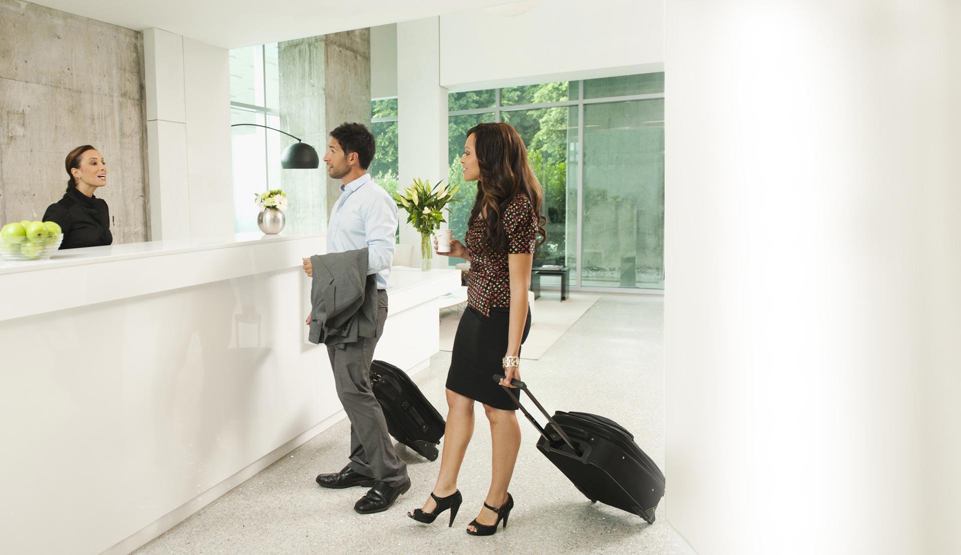 Geschäftsreisende mit Koffer an Hotelrezeption
