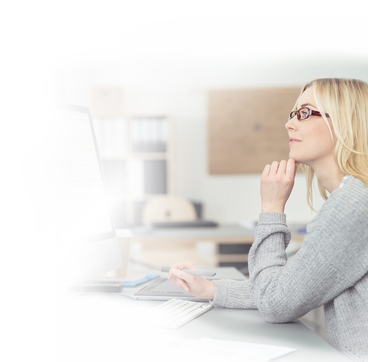profile of a woman with glasses who is looking at a desktop