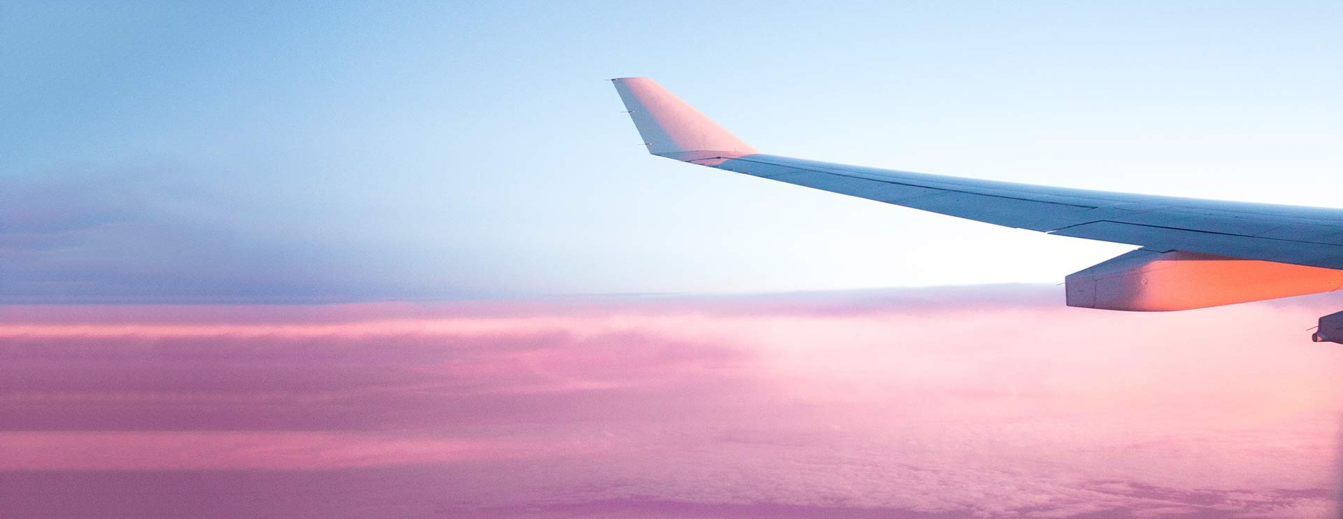 Airplane wing at sunset capturing the ease of AirPlus travel trade payment solutions