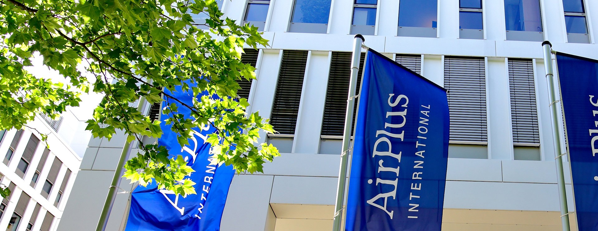 Two blue flags with AirPlus on in front of a building