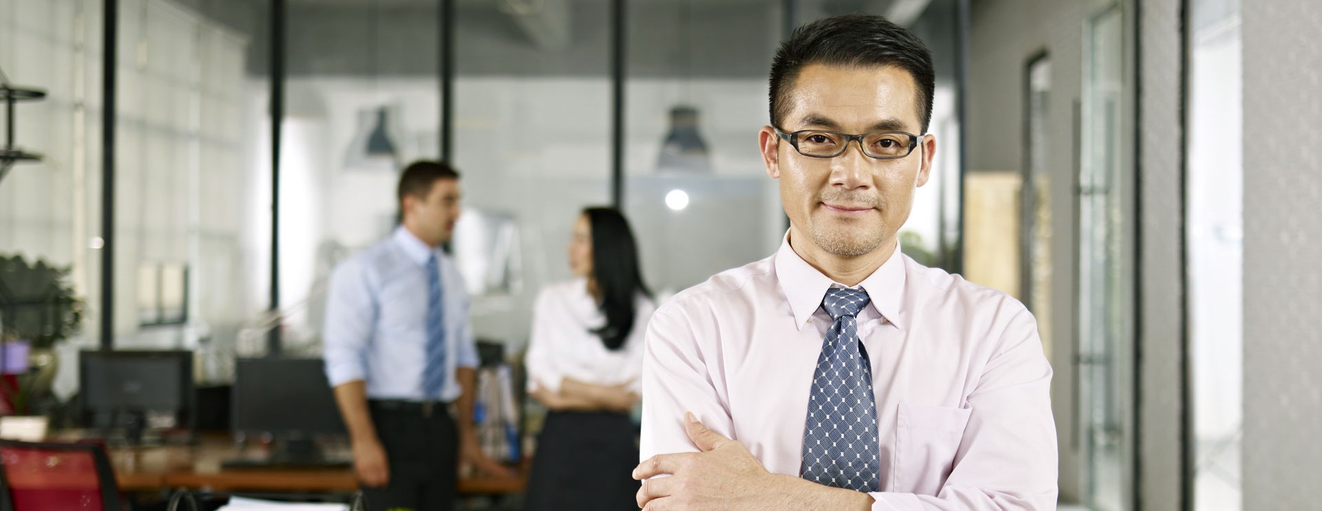 an asian bussinessman in white looking into the camera in the office