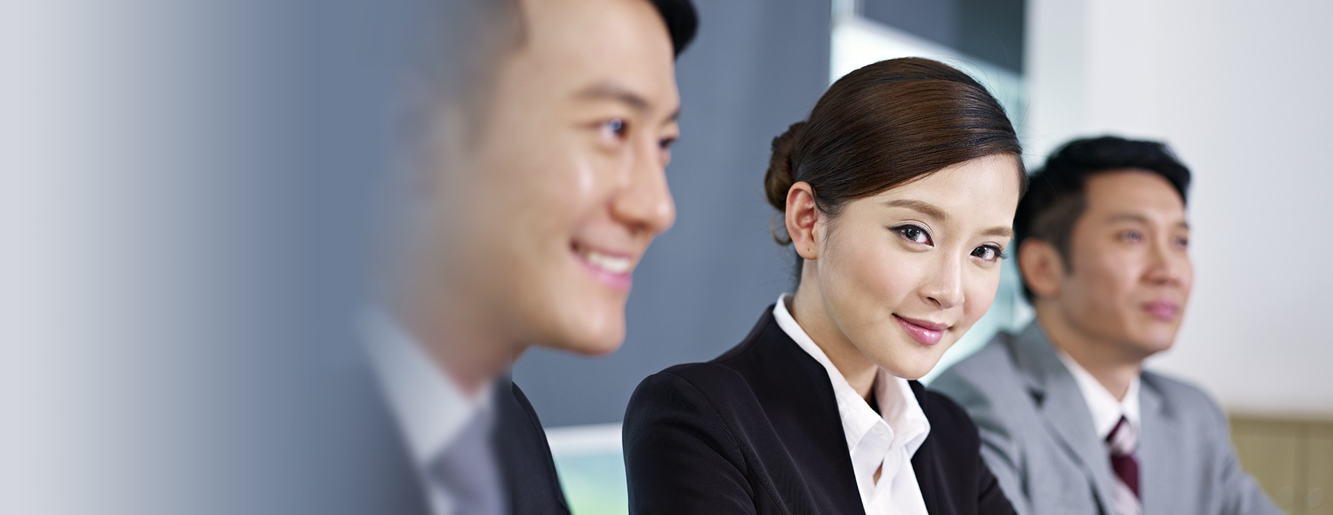 a young asian woman smiling to the camera in a conference,two businessmen sitting beside