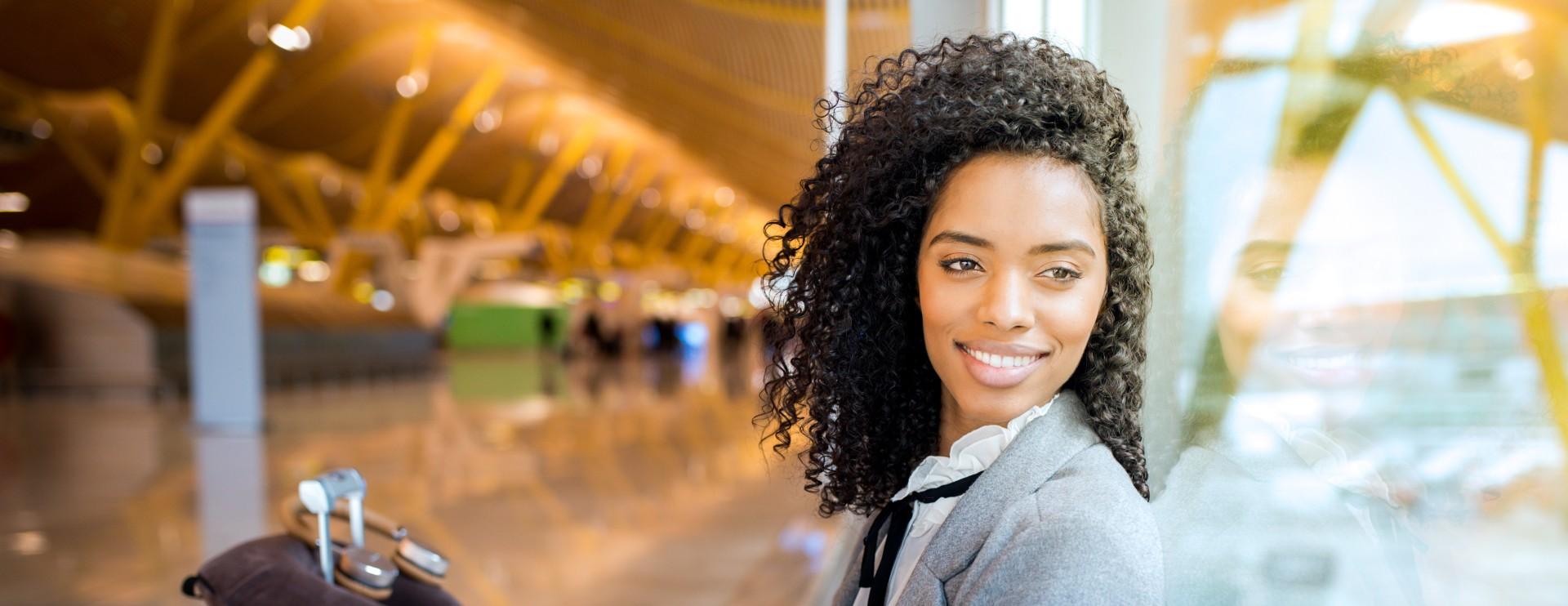 Geschäftsfrau wartet mit ihrem Koffer am Flughafen