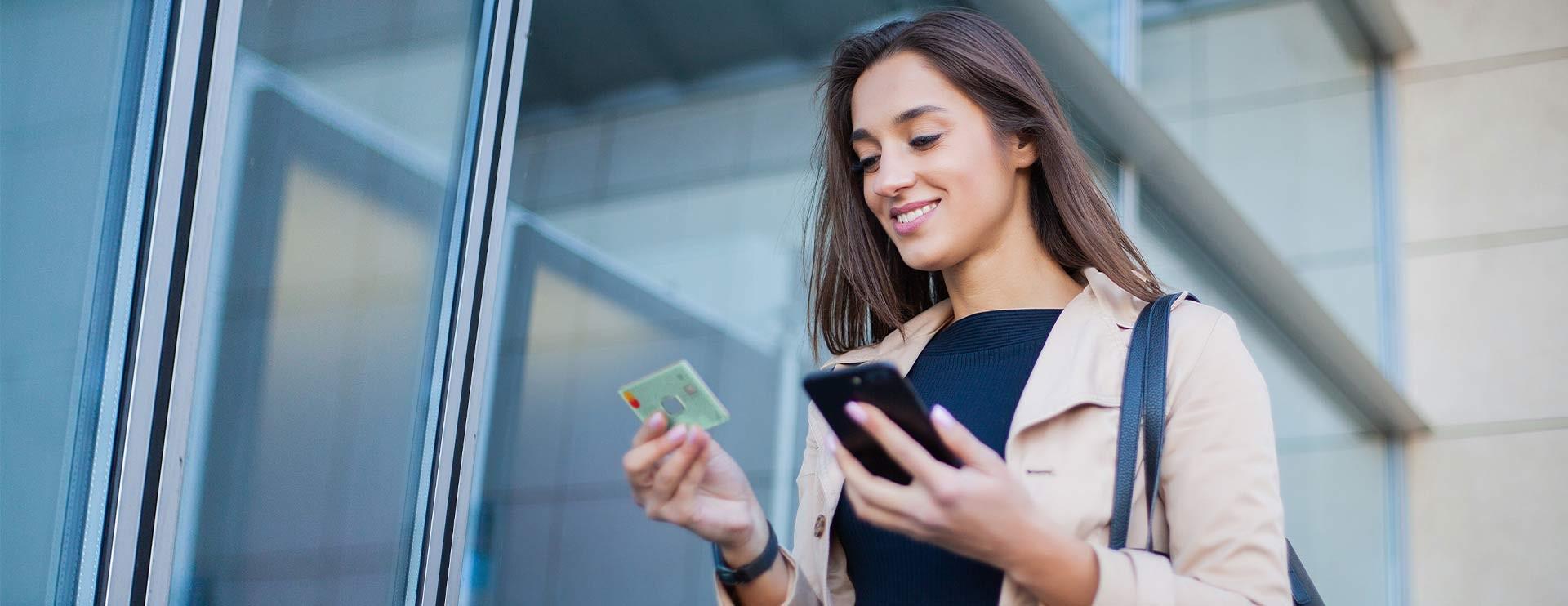 Geschäftsfrau betrachtet AirPlus Corproate Card in ihrer Hand.