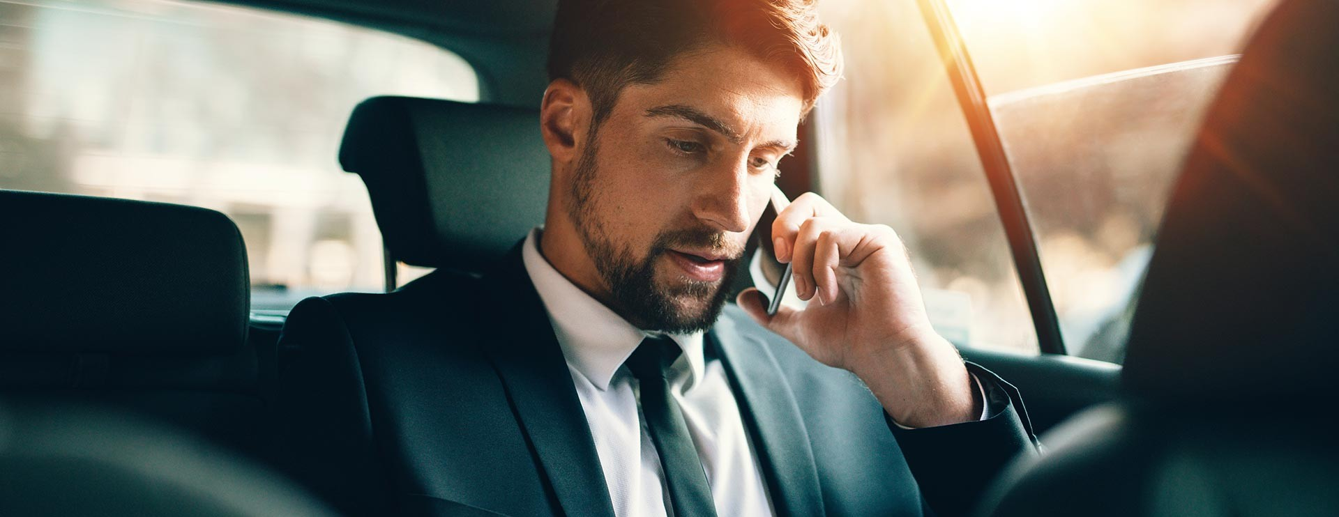 Businessman on the phone travelling in a car