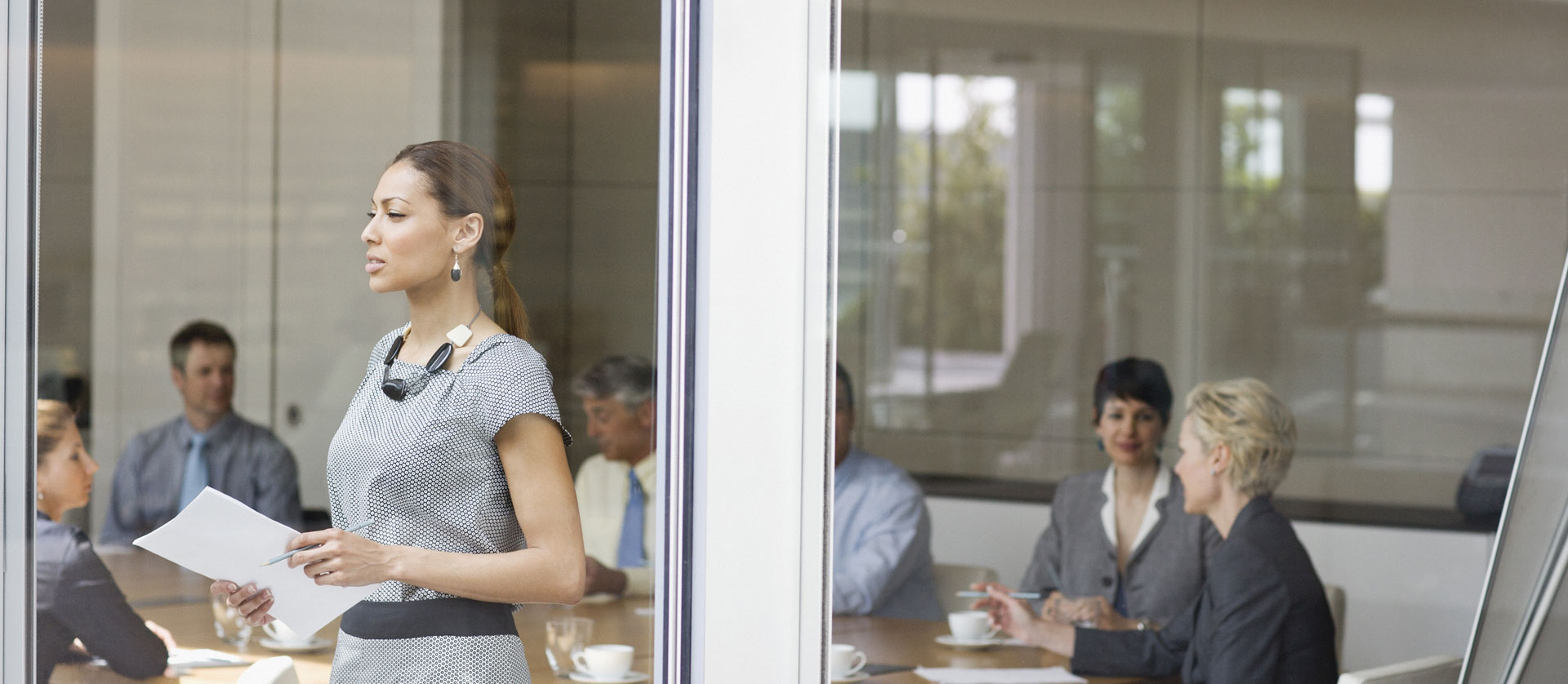 businesswoman in front of conference room window with people seated at a table in the background