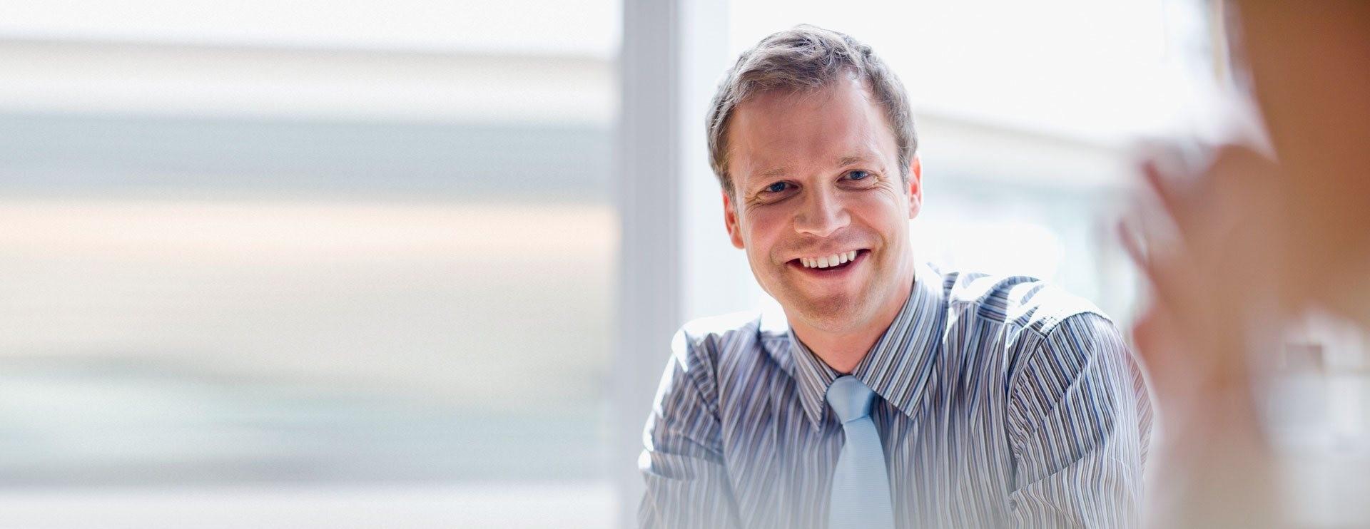 Uomo che sorride durante una riunione