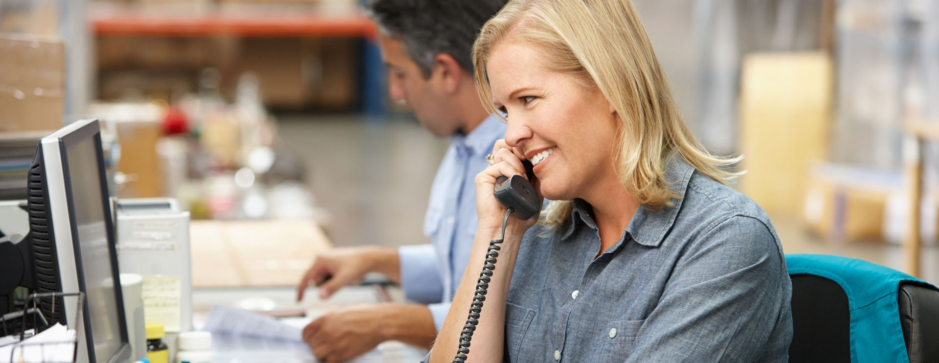 Femme souriant au téléphone devant un ordinateur