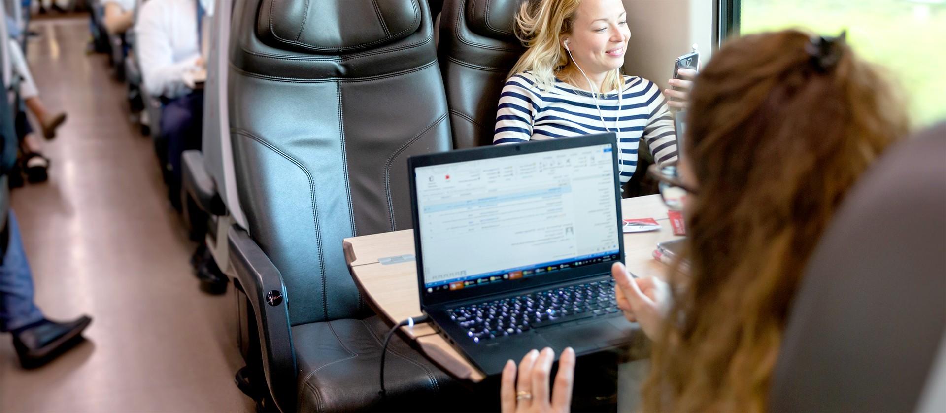 Geschäftsreisende sitzt im Zug mit aufgeklapptem Laptop