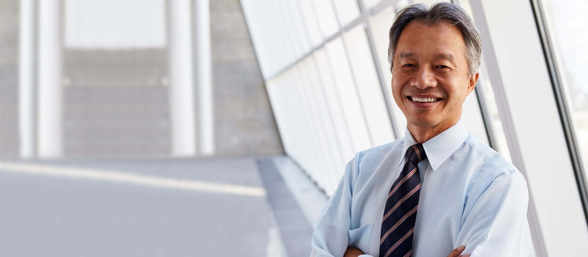 a senior asian businessman smiling to the camera beside the window