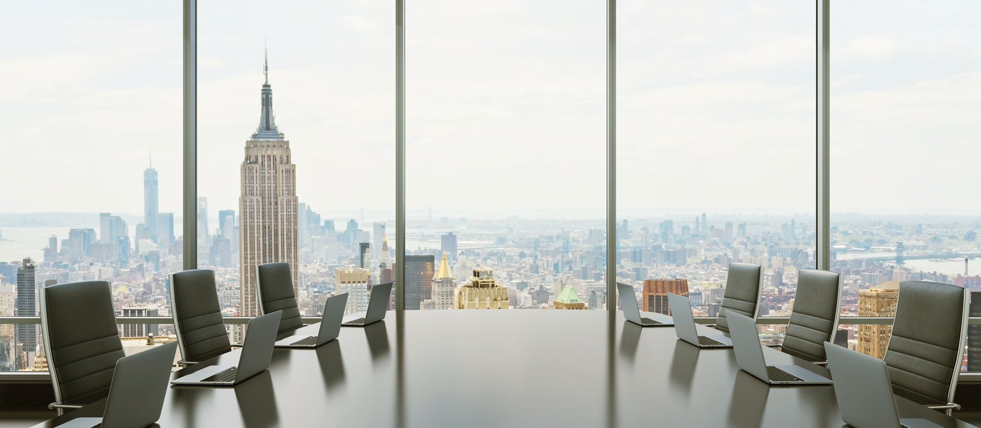 End of the conference room table with a view out over a city skyline