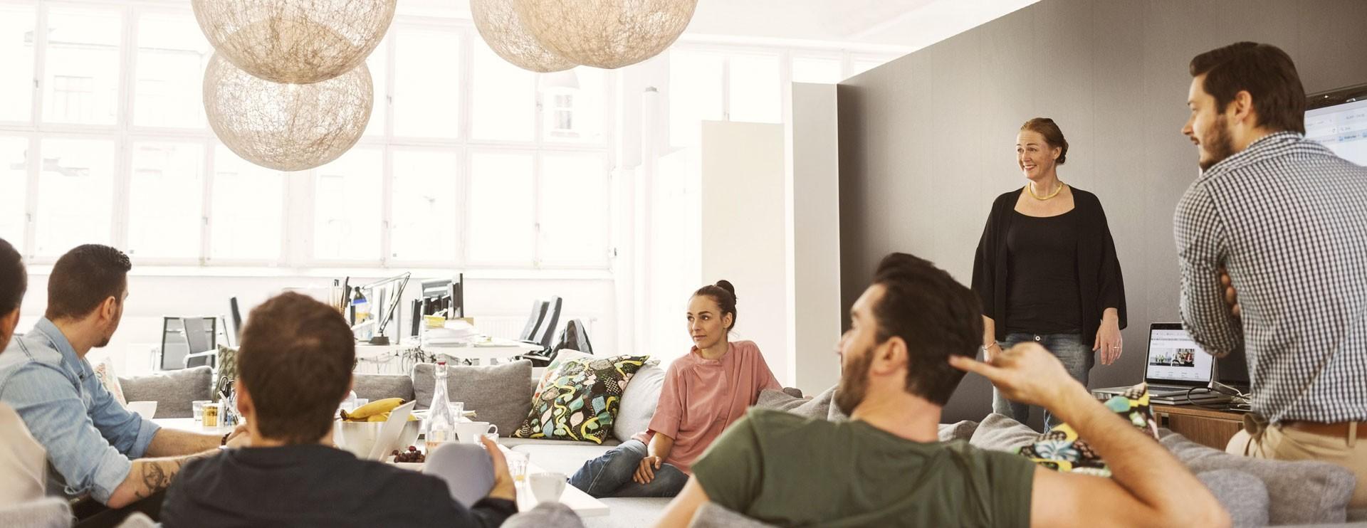Gruppe von jungen Leuten sitzt und steht in einem Raum und diskutiert