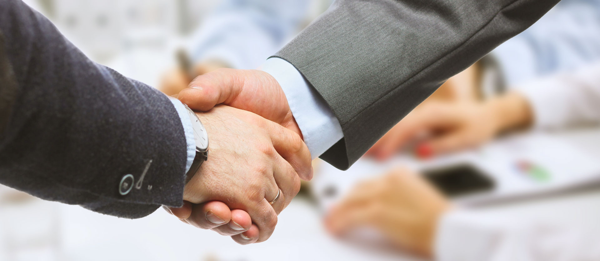 close up of two businessmen shaking hands in a meeting setting