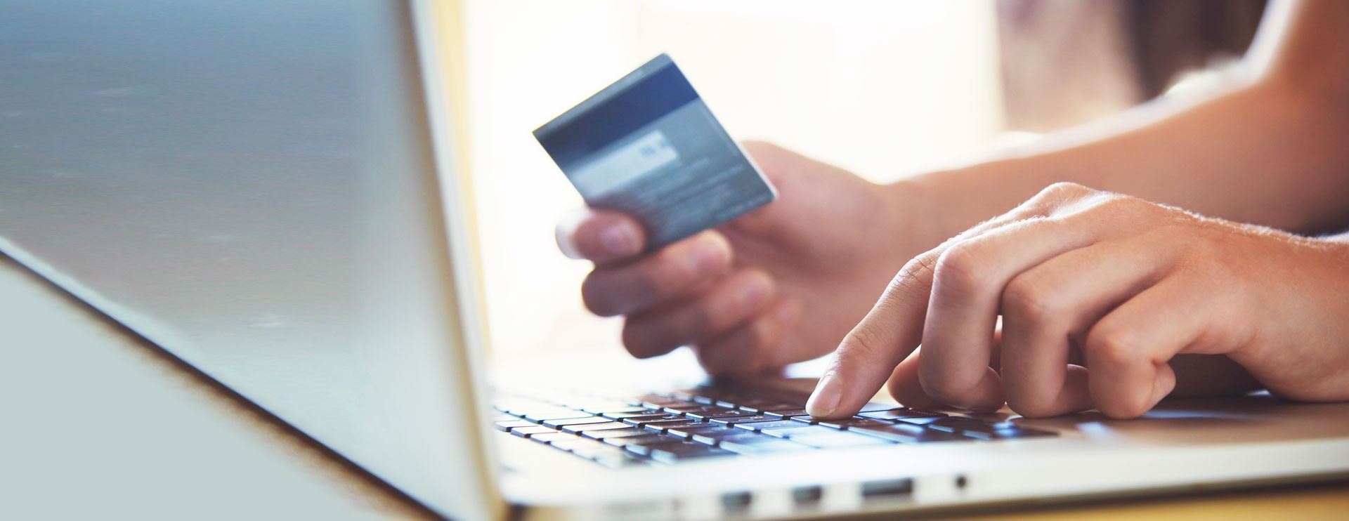 hand holds a credit card in front of a laptop