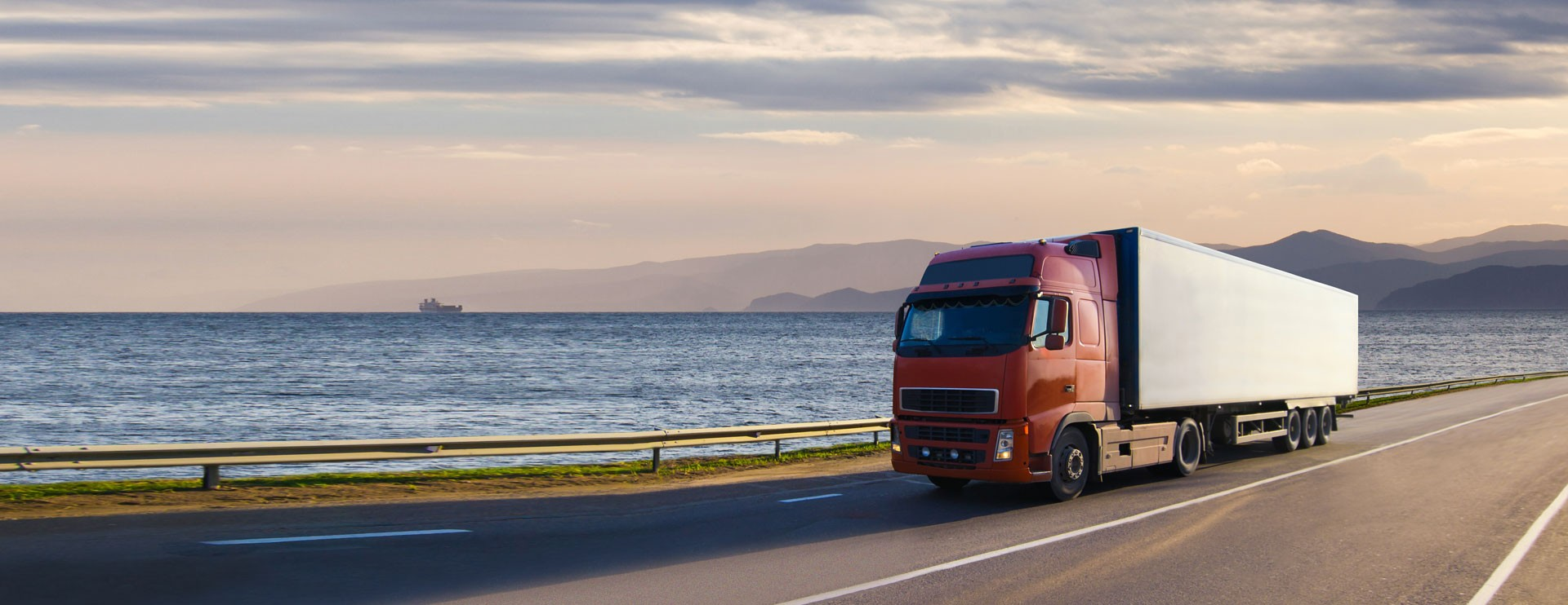 semi-truck on the highway with the ocean in the background