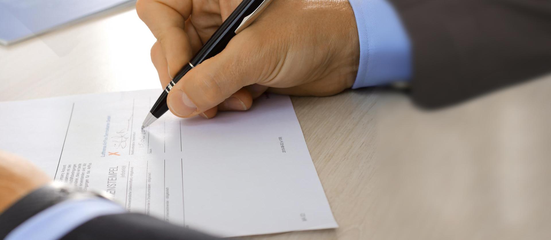 Eine Männerhand unterschreibt einen Vertrag