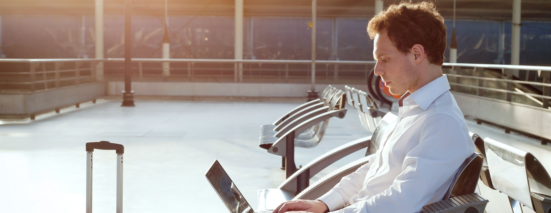 traveler sitting in airport with laptop open