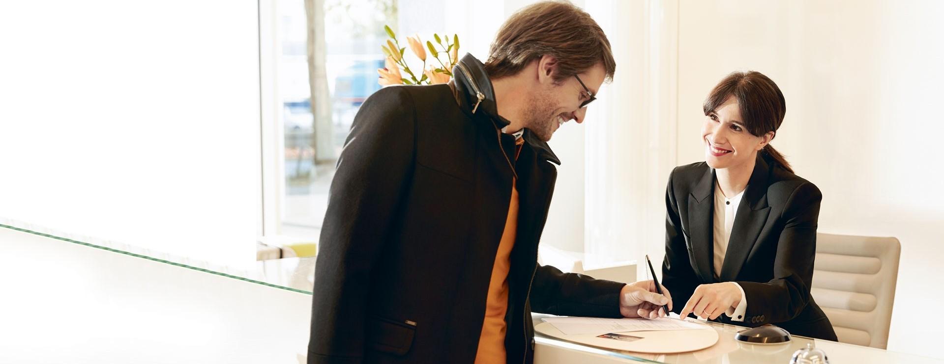 Business traveler at reception desk.