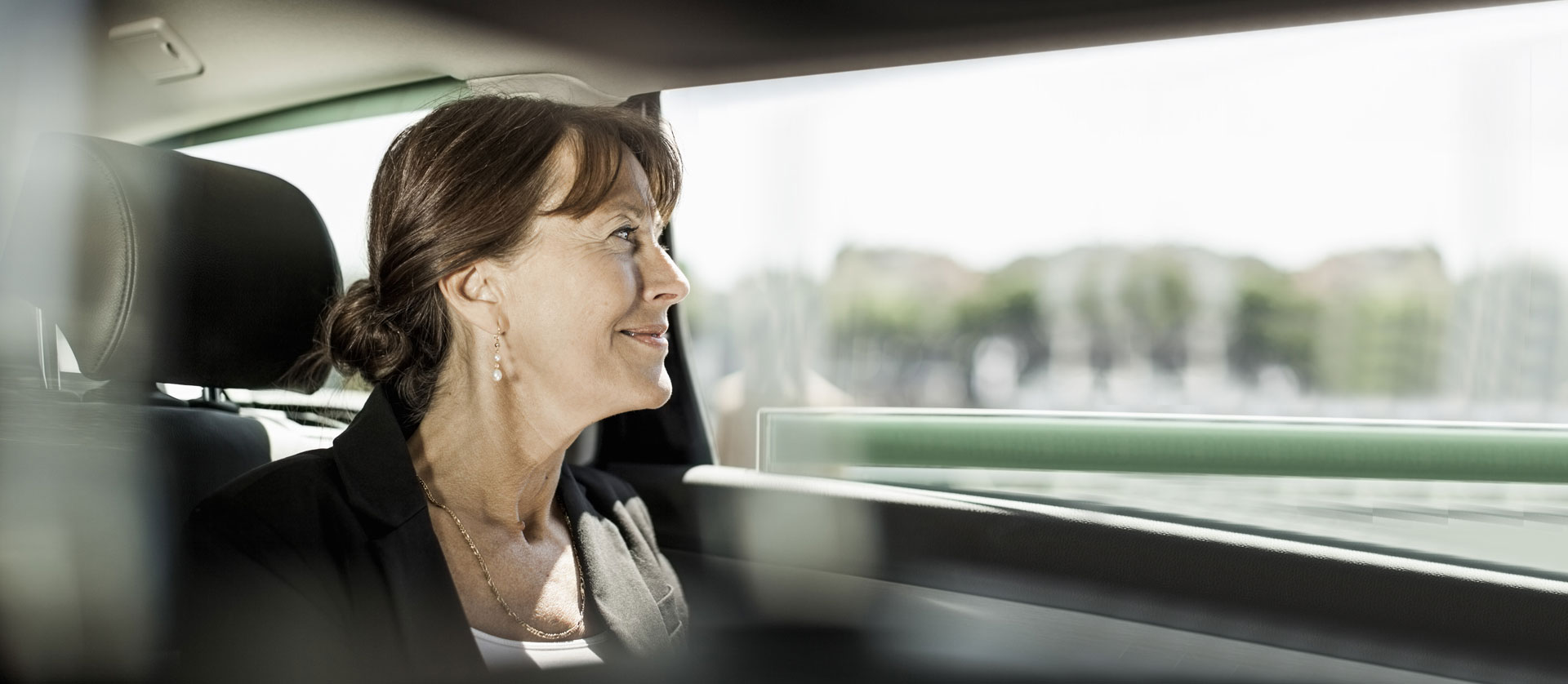 Woman looking outside from backseat of a car