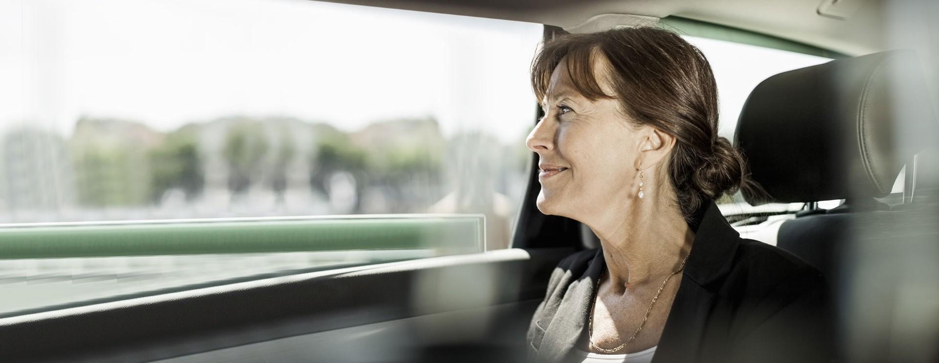 Vrouw kijkt naar buiten vanop de achterbank van een auto