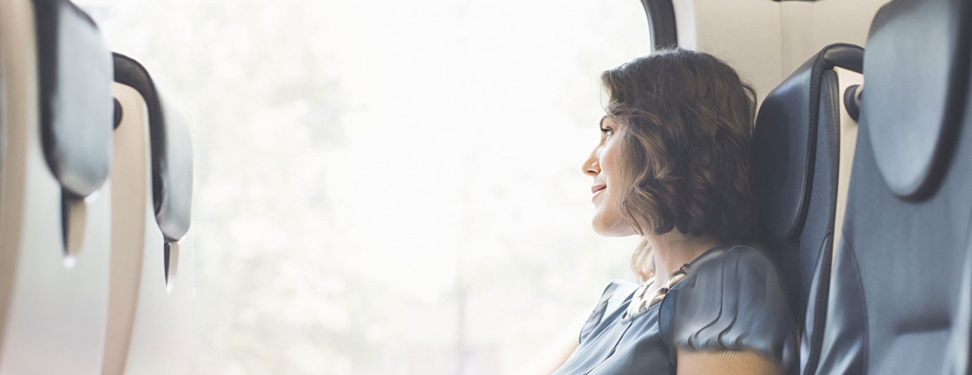 Woman sitting in a train lookig out the window.