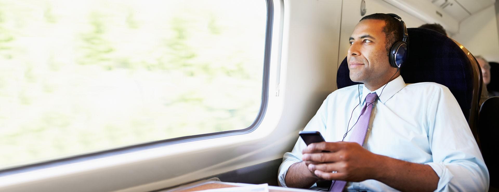 Man in trein met mobiel