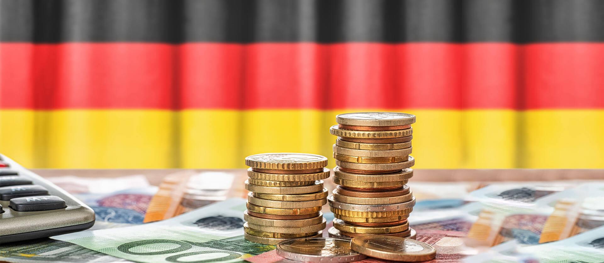 Die deutsche Flagge und Münzen stellen die befristete Senkung der deutschen Mehrwertsteuersätze dar.