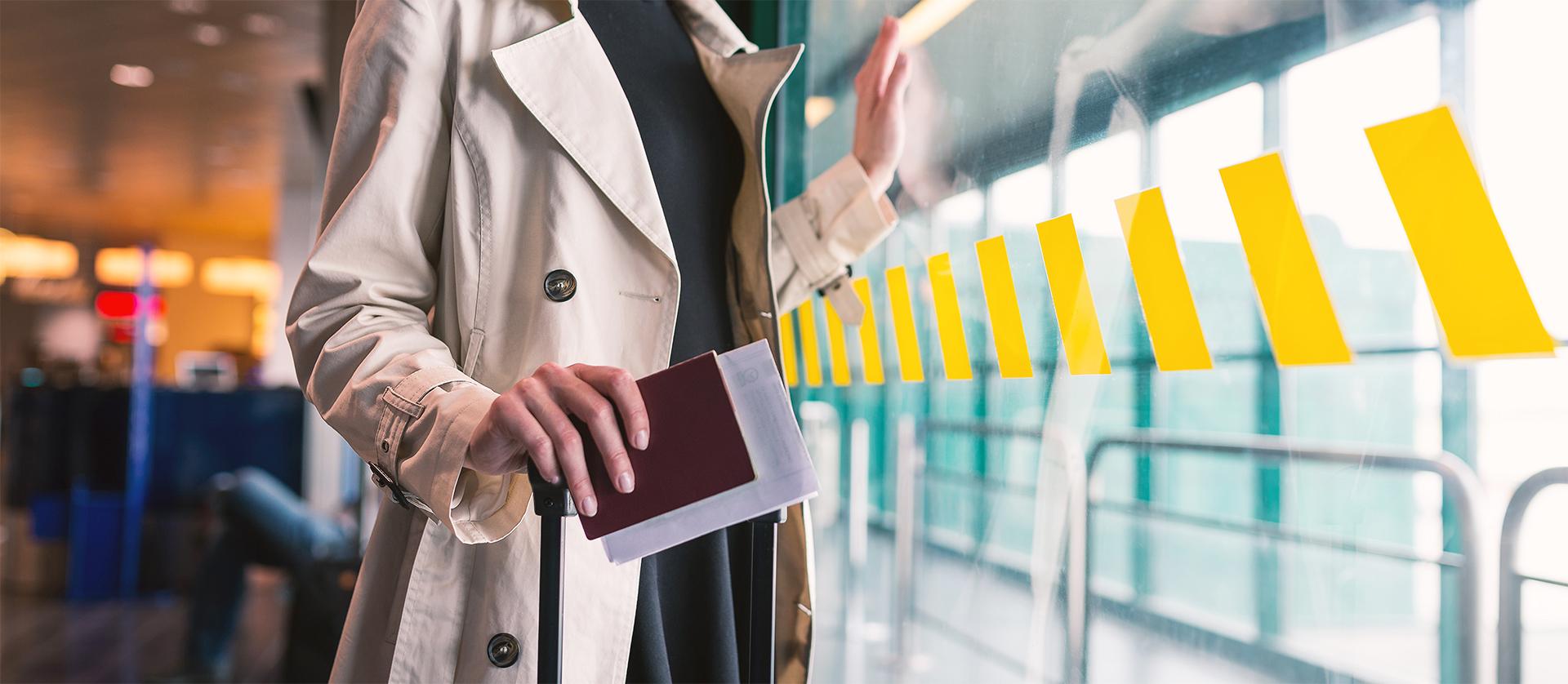 Frau hält Reisepass und weitere Dokumente am Flughafen bereit