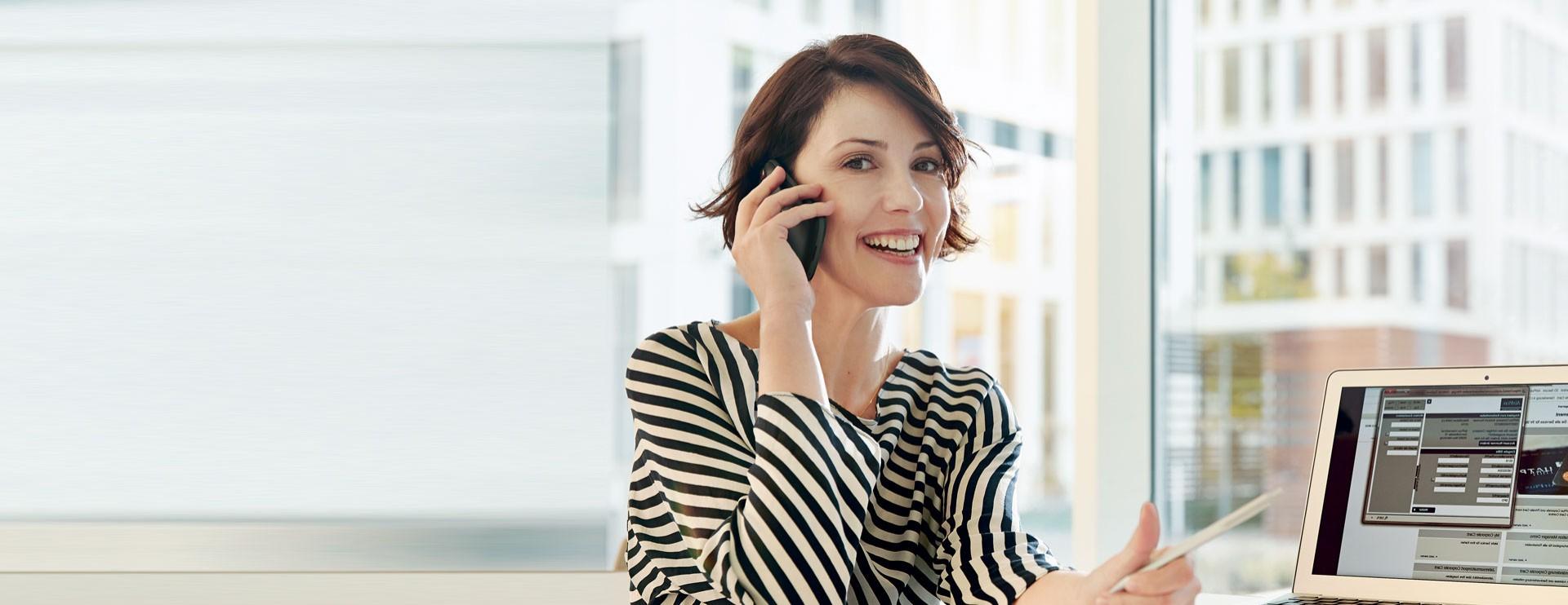 Frau an einem Mobiltelefon vor einem Computer
