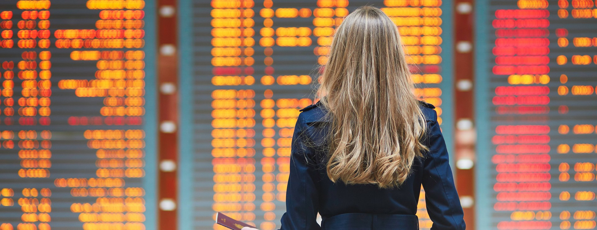 Woman standing in front of arrival/departure board at airport