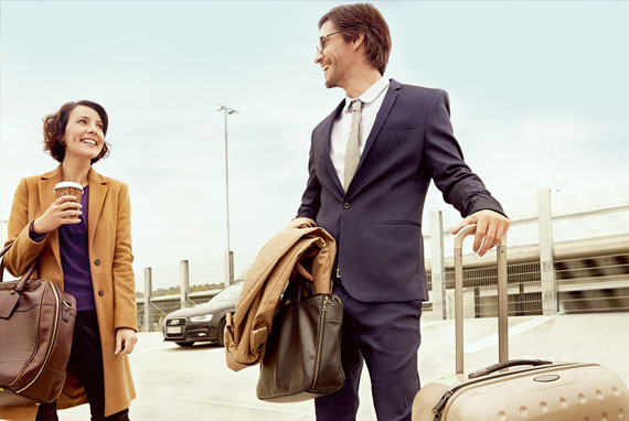 Business traveler man and woman on parking deck talking and smiling: Business Travel Management