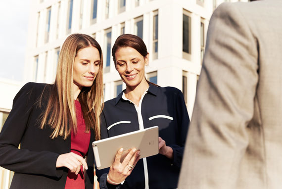 Two businesswomen looking at a tablet, We are specialists – in meeting your needs.